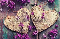 stock-photo-postcard-with-two-decorative-hearts-and-fresh-lilac-flowers-on-green-aged-wooden-backgro
