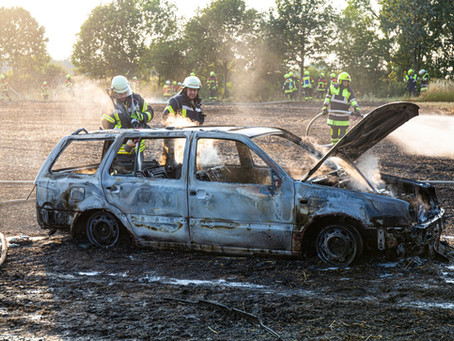 Auto und Feld in Flammen