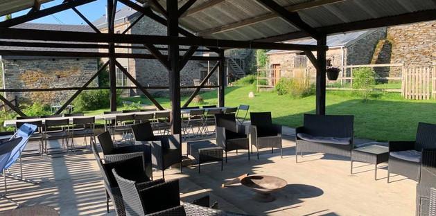 Terrasse couverte avec espace repas et salon d'extérieur autour d'un brasero