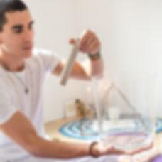 Felipe Sucupira, terapeuta sonoro tocando tigela de cristal transparente