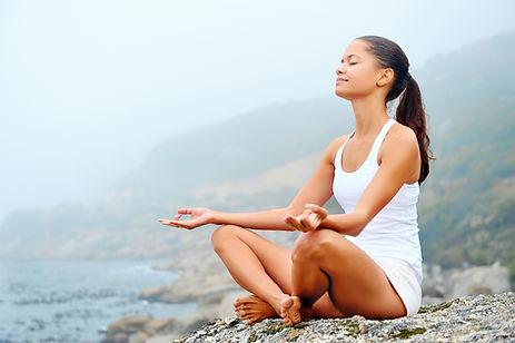 En kvinne sitter i yoga-posisjon