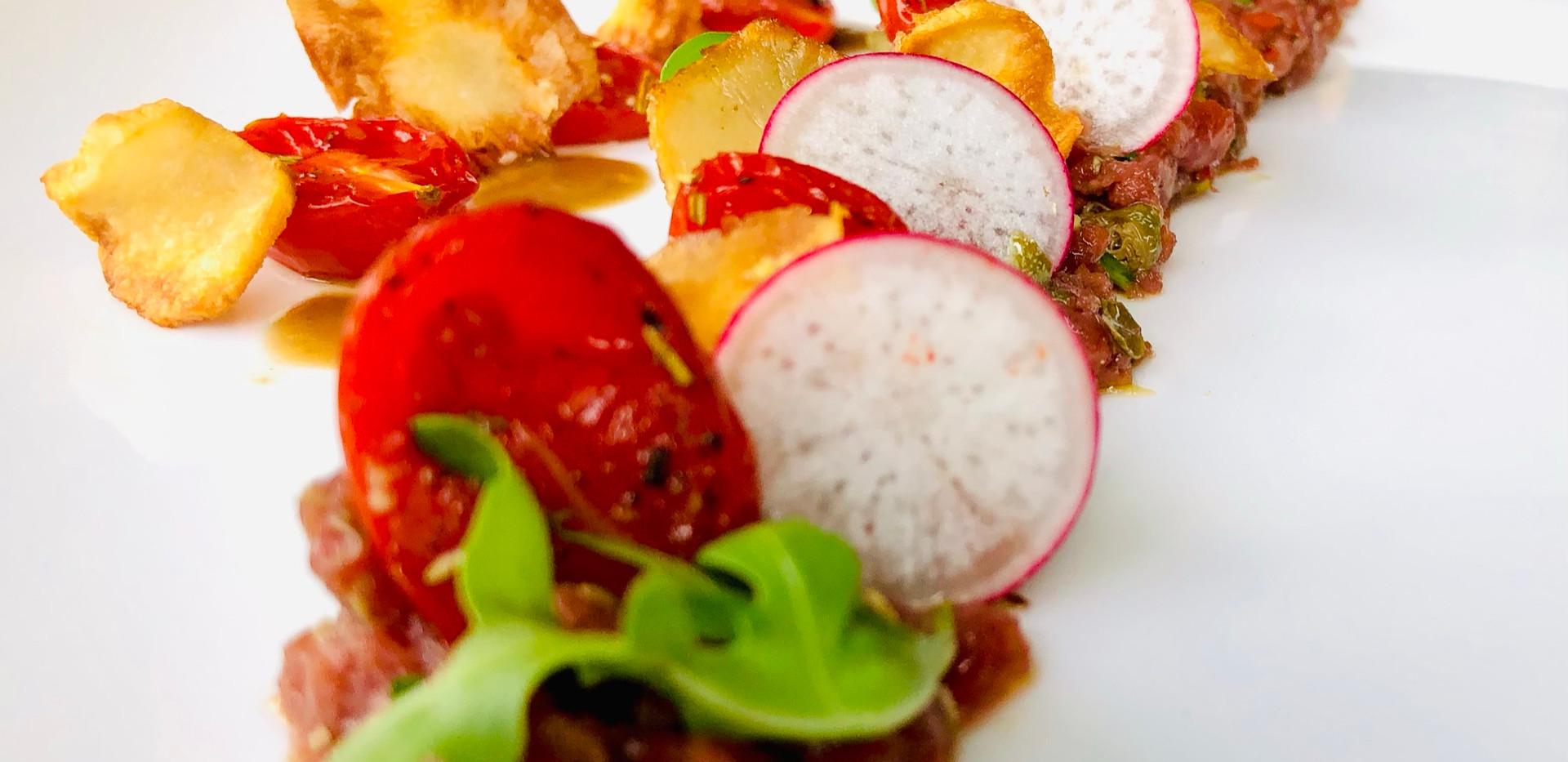 Tartare di manzo marinato con vinaigrette alla senape, pomodorini confit  e chips di topinabur