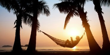 man relaxing in a hammock at sunset