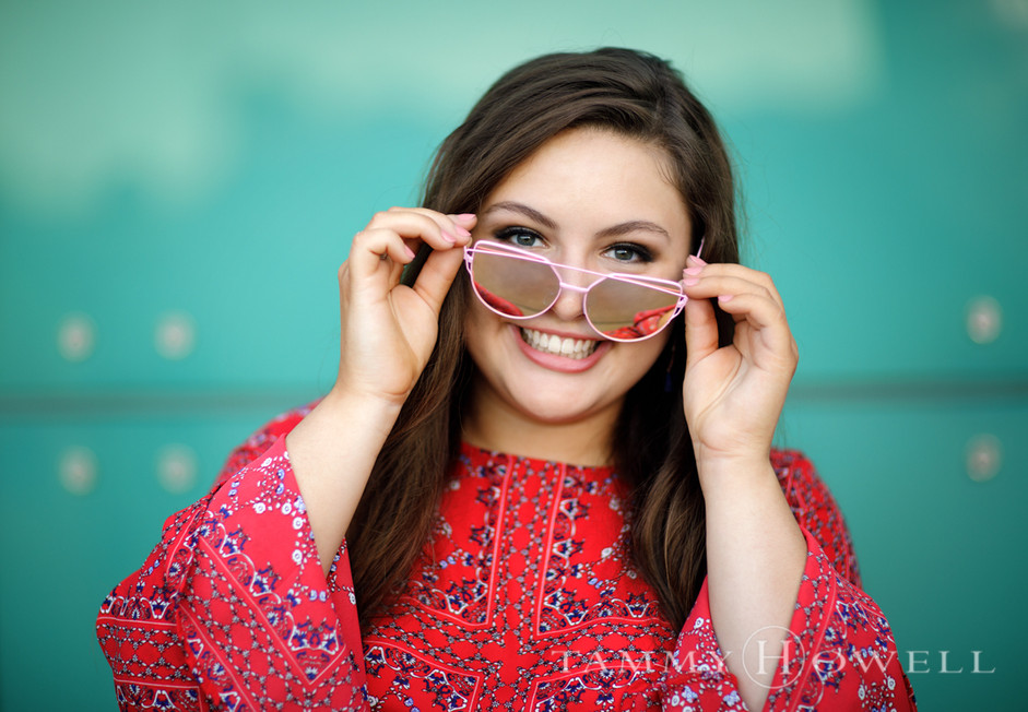 Cute senior with sunglasses and green wall