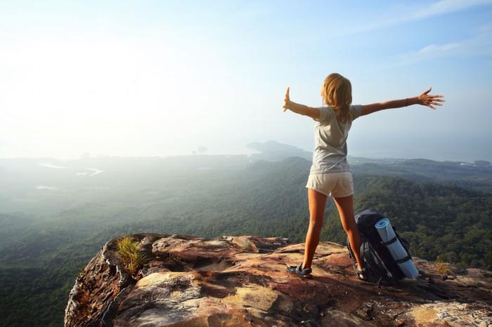Foto de uma mulher no topo de um penhasco com os braços abertos e uma mochila de viagem ao lado