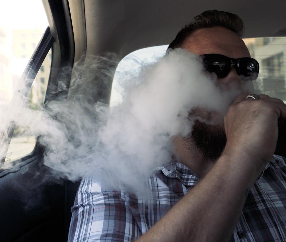 Jacob Ooten, army veteran smokes marijuana in the backseat in Colorado Springs, Colorado.