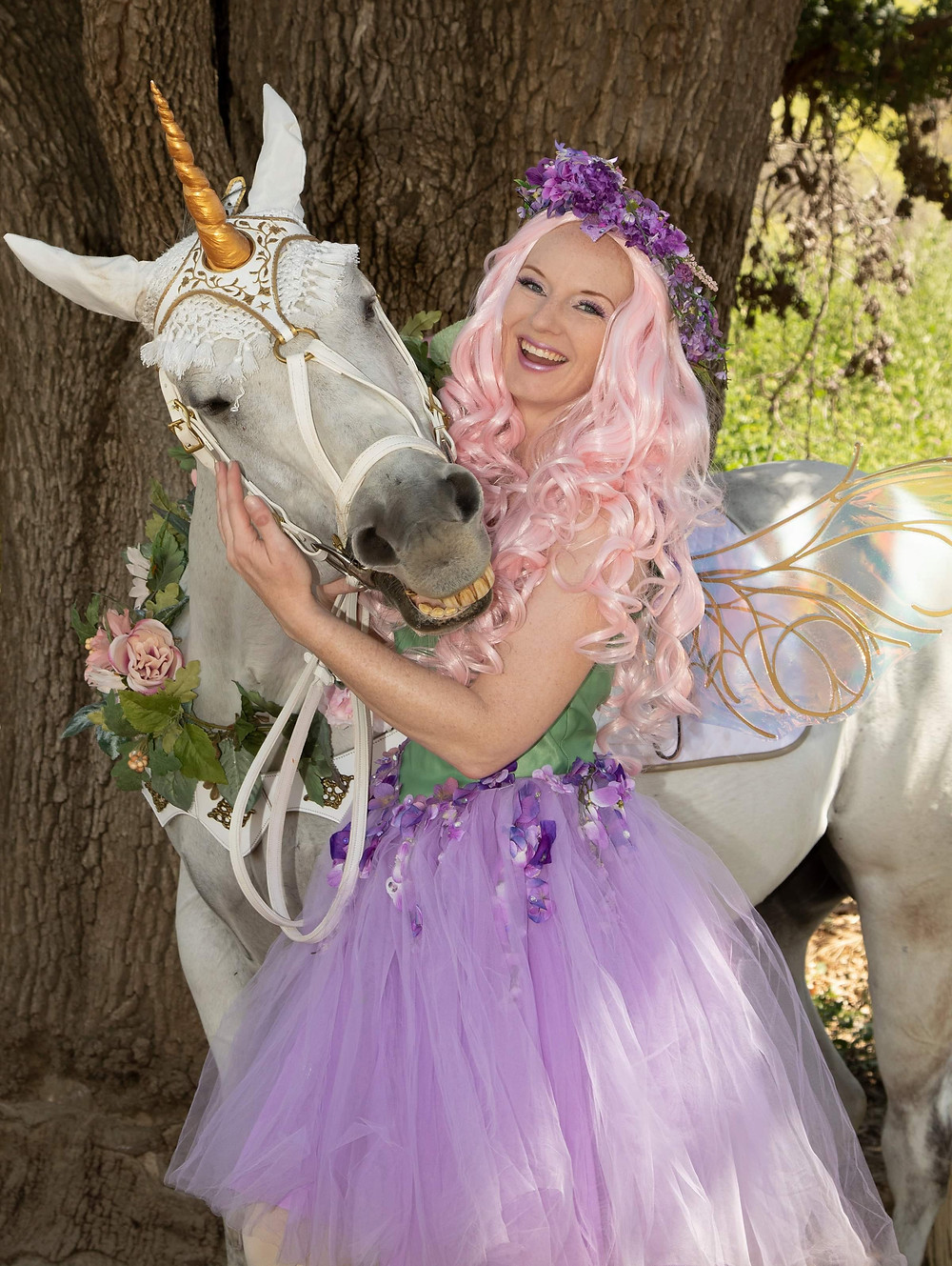 Milo the Unicorn Smiles for a photograph next to a woman wearing a purple and green fairy costume.