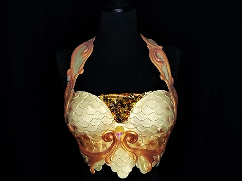 A mermaid bra top costume rental in Los Angeles made of silicone for swimming with gold, white, and scale decorations.