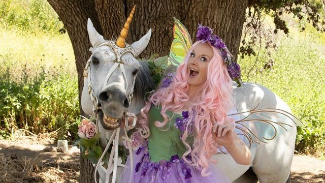 A horse dressed as a unicorn makes a silly face next to a fairy.
