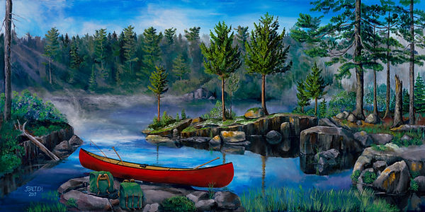 A red canoe rests on a rock in the beautiful Boundary Waters of Ely, Minnesota next to packsacks and paddles