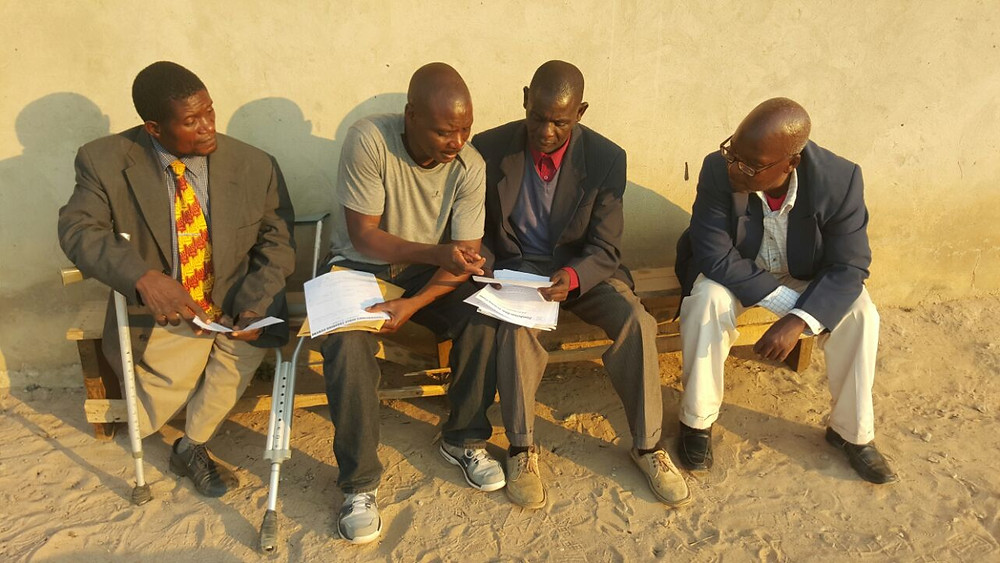 Apostle Jim Phiri reviewing school materials with Bishpo Gift and two of the teachers