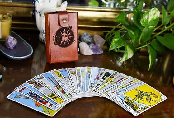 This is a picture of a tarot deck and some crystals; rose quartz, amethyst, and blue calcite. This picture also contains plants, and is made to imitate an altar space.