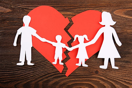 Paper cutout silhouette of a family split apart on a paper heart, divorce concept.jpg