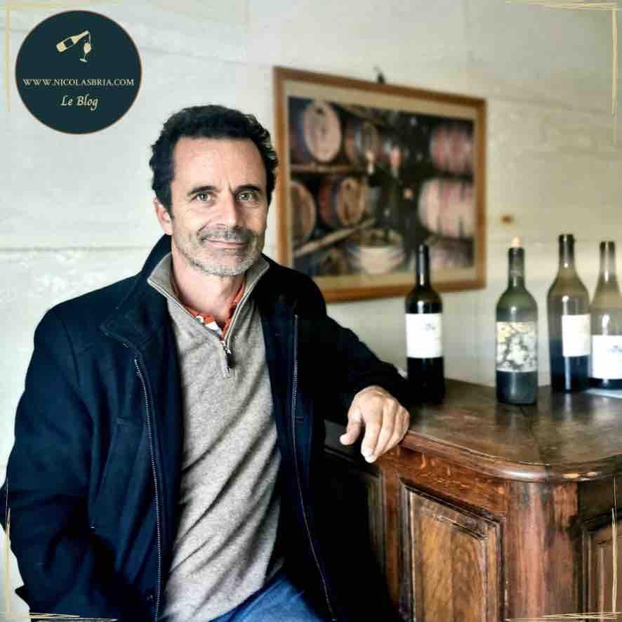 On voit Cyril Marès, vigneron du Mas des Bressades, accoudé au comptoir de dégustation. Des bouteilles sont ouvertes sur le comptoir. dans le fond, un portrait de Roger Marès, son père.