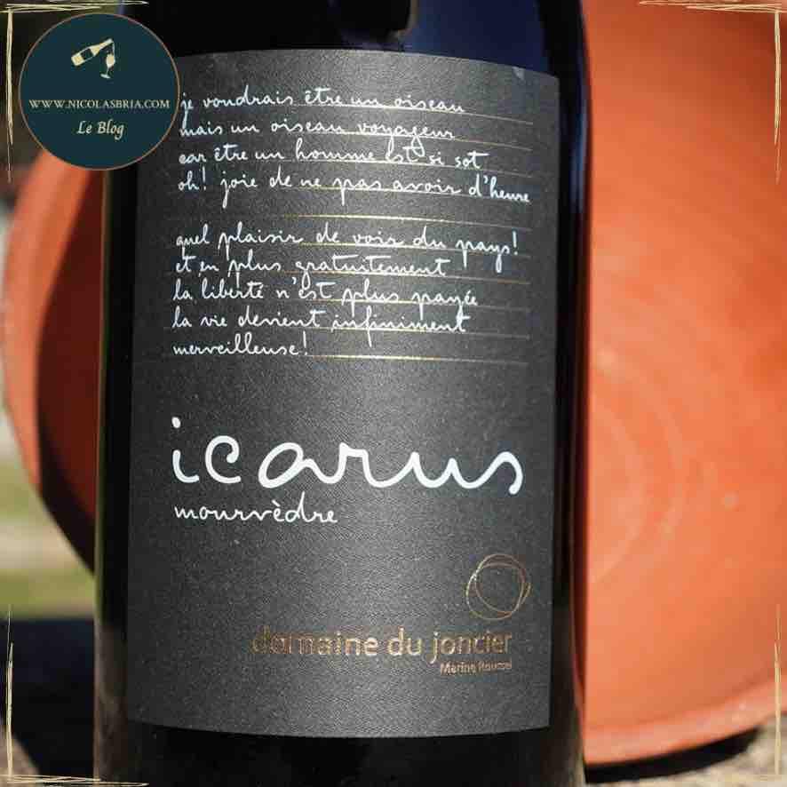 on y voit la cuvée Icarus du domaine du joncier. l'étiquette est noir avec des écriture blanche. dans le fond un vase en terre cuite renversé, pour symbolisé l'amphore dans lequel le vin est élevé.