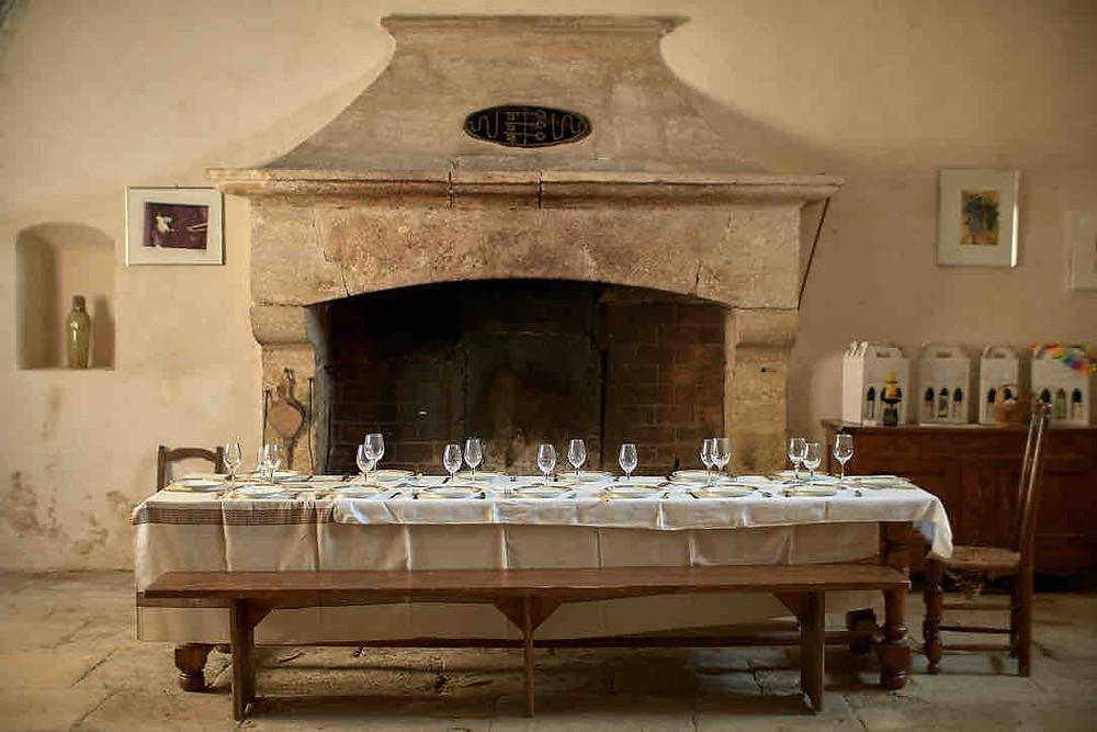 On y voit l'ancienne cuisine du domaine. Au fond, la grande cheminée. Devant une table en bois, dréssée d'une nappe blanche