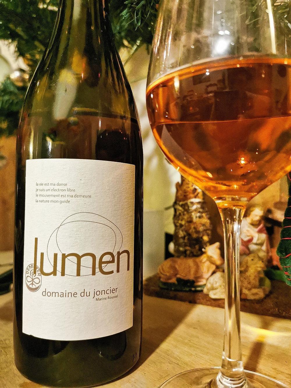 On y voit une bouteille de vin blanc qui se nomme Lumen. Un verre rempli. la couleur du vin est orange. dans le fond, un sapin et une crèche