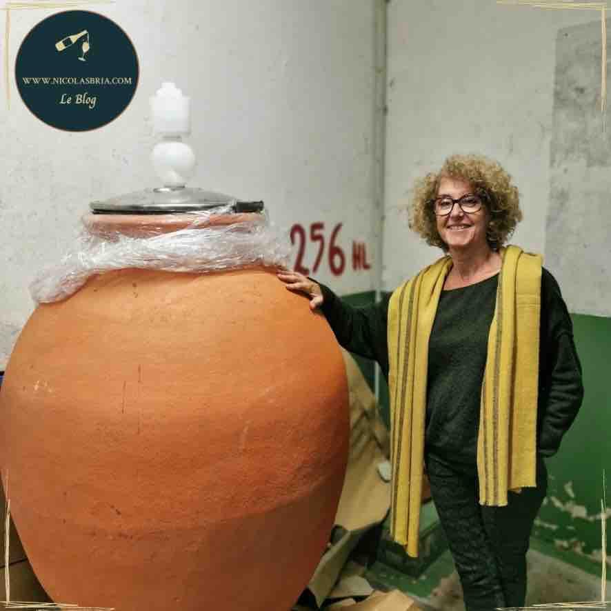 A gauche de la photo, Marine Roussel, la vigneronne. Elle sourit et pose sa main droite sur un grande amphore en terre cuite.