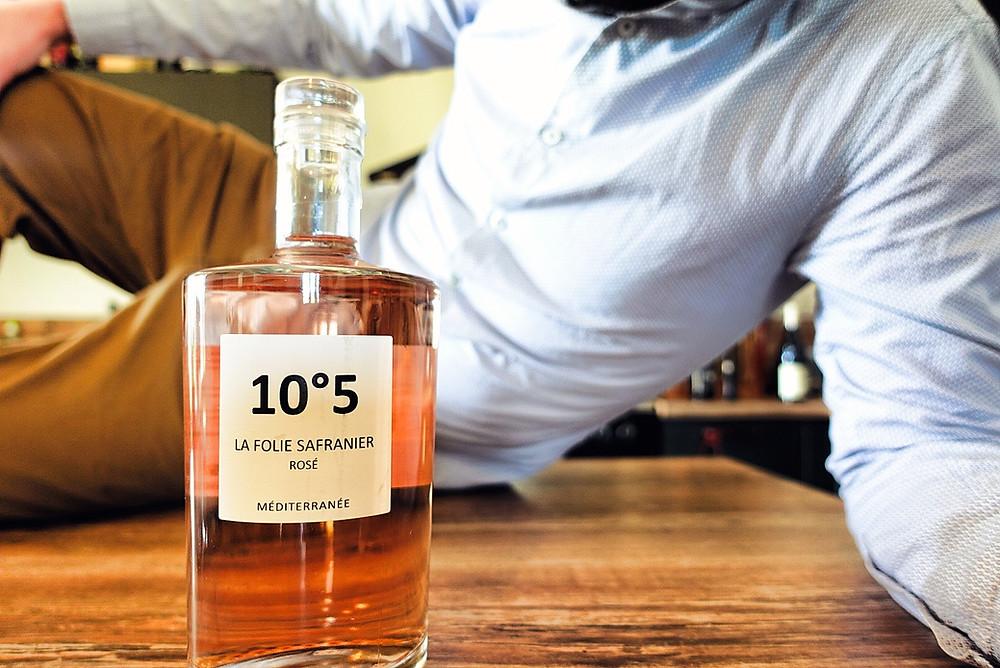 On y voit une bouteille de rose en mode de bouteille de parfum, type Channel n°5.