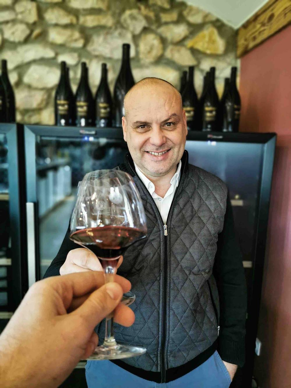 On voit Stéphane Charrier, vigneron, un verre à la main, en train de trinquer. il sourit.