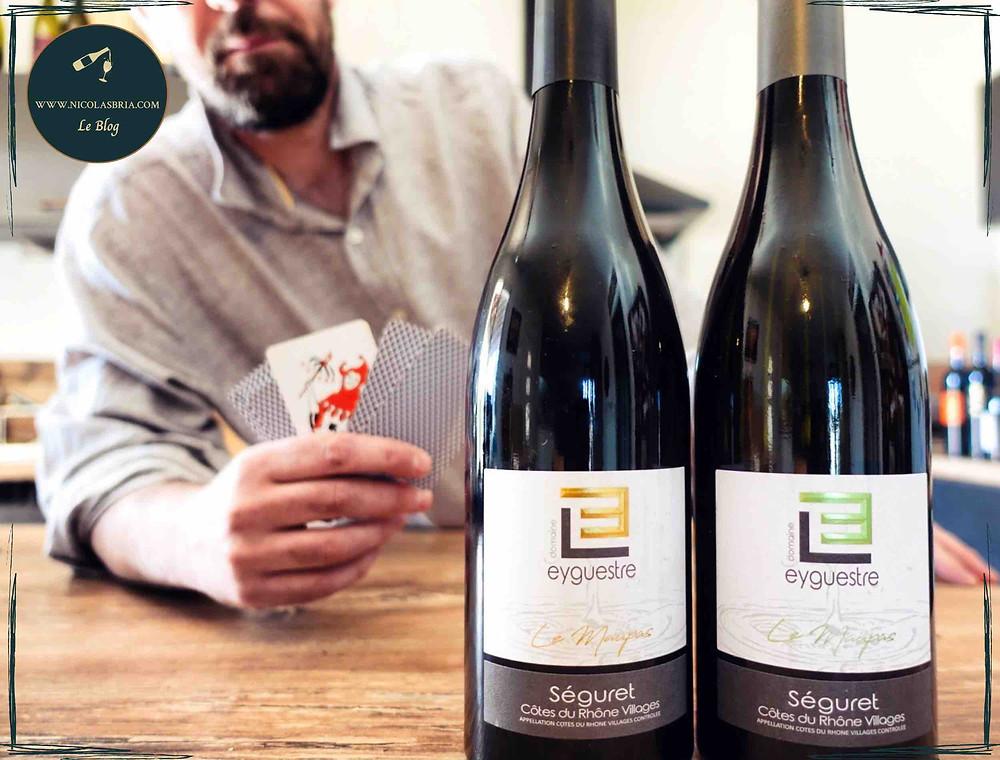 """Deux bouteilles sont posées sur une table. il s'agit des cuvées """"Le Maupas"""" en blanc et rouge. derrière, Nicolas Bria en train de jouer aux cartes"""