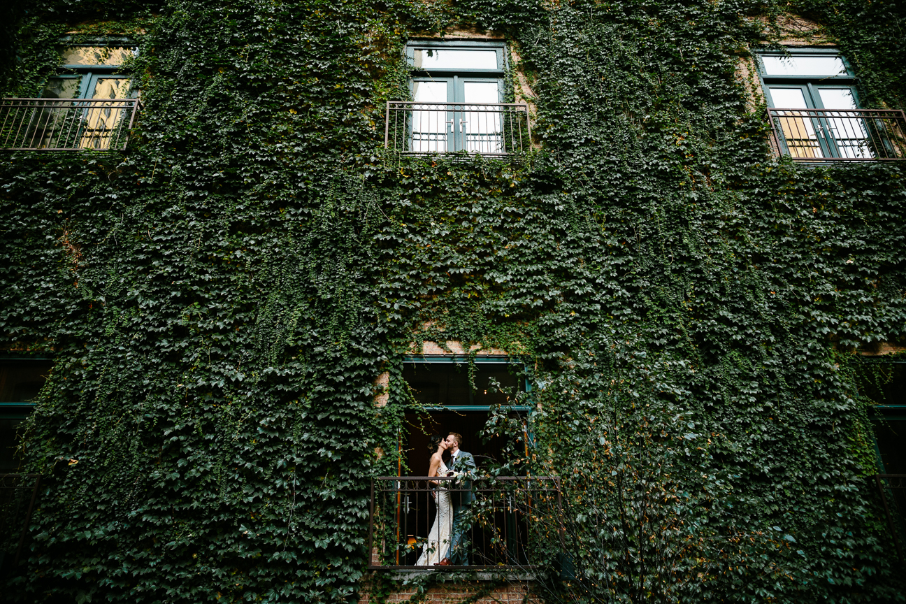 couple on a balcony ivy covered wall