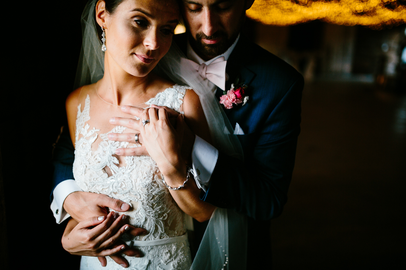 newlywed embrace in a barn dim light
