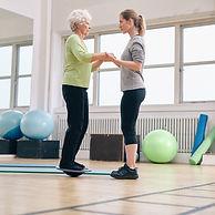 Trainer exercising with senior