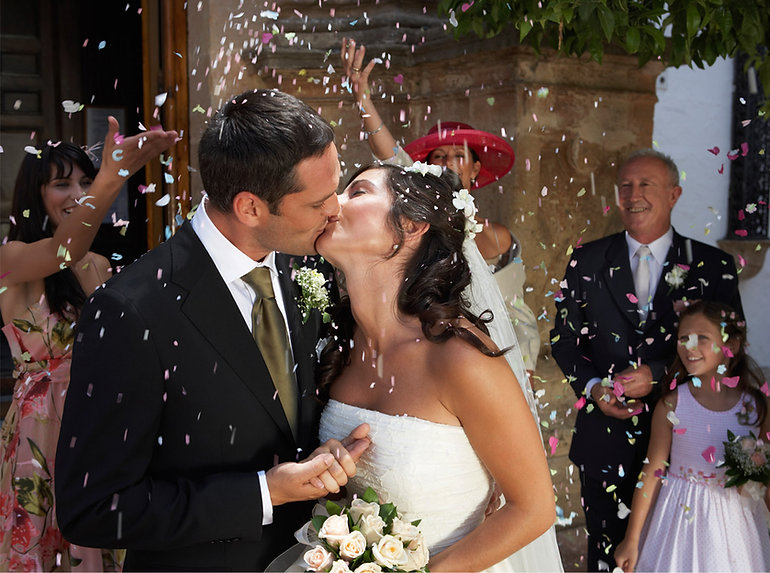Happy Bride and Groom in confetti shower outdoors the church | stunning photography