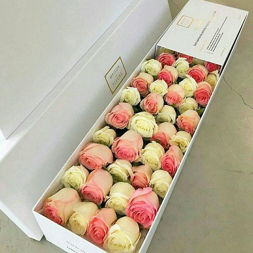 белые и розовые розы в длинной прямоугольной коробке