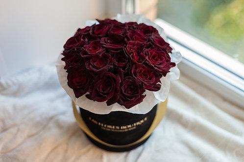 красные розы в черной шляпной коробке