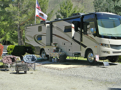 RV with flags, a dog, coffee table, two chairs and a small table