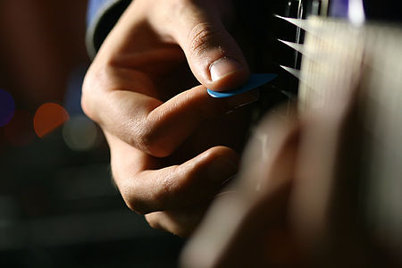 hand plucking guitar strings