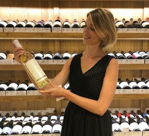 Margot présentant une bouteille de Sauvignon blanc bordelais