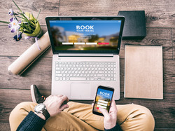 Man using a laptop and smartphone for booking hotel online.jpg Tour reservation, Screen graphics are