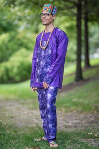 Groom from the Caribbean with a dashiki-inspired purple outfit standing casually and smiling looking towards the horizon.