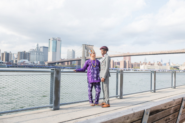 After ceremony officiated by queer officiant at Once Upon A Vow, two grooms looking lovingly at each other, one wearing a purple dashiki-styled outfit; the other, a charcoal grey suit with red wine bow tie with the Brooklyn Bridge in the background.