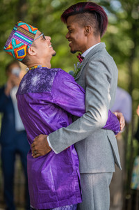 """Two grooms from the Caribbean embracing more loosely this time following their first married kiss looking at each other and smiling as if to say, """"yes, we did it!"""" after their ceremony, which was officiated by the queer officiant from Once Upon A Vow."""