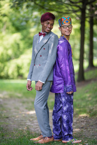 Black grooms standing back to back, playfully looking over their shoulders at each other; the one to the left is in a charcoal grey suit with red wine accents and red wine hair and the other is in a dashiki-styled purple suit with a traditional hat from his native country before their Brooklyn ceremony officiated by queer officiant from Once Upon A Vow.