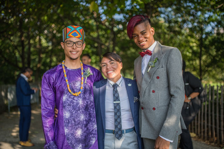 Two grooms from the Caribbean standing at least 6-10 inches taller than their queer officiant from Once Upon A Vow who is sandwiched between them arm in arm; all are smiling and look good with lots of trees and some guests in the background.