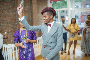 Groom with charcoal grey suit with red wine buttons, bow tie, and hair smiling and excited to toss the boutonnière with his husband beside him and a crowd of guests in the background ready to catch it!