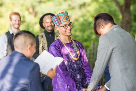 Two grooms from the Caribbean holding hands and reacting to something funny their queer officiant from Once Upon A Vow just shared that resonated strongly with the groom wearing a charcoal grey suit; he started laughing and broke the special wedding gaze between them while guests in the background joined in with their own chuckles.