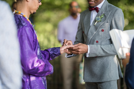 Two grooms during the ring exchange portion of the ceremony officiated by the queer officiant at Once Upon a Vow; the one in the charcoal grey suit with red wine accents places the ring in the left ring of his beloved in his purple dashiki-styled wedding outfit.