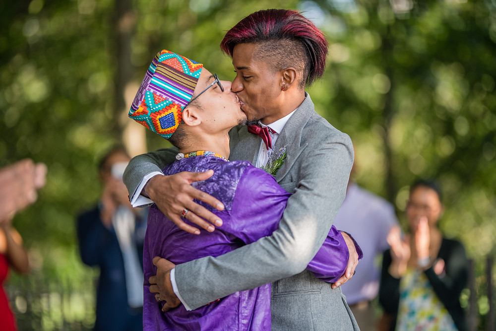 Two grooms from the Caribbean fully embracing and kissing as they close out their ceremony officiated by LGBTQ officiant from Once Upon A Vow with guests clapping in the background.