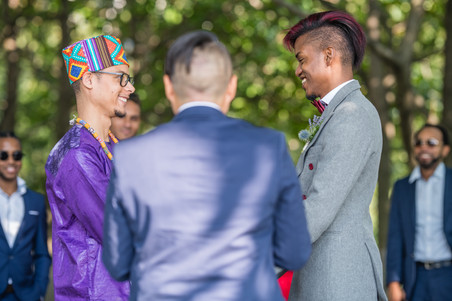 Two grooms from the Caribbean holding hands and looking at each other smiling as instructed by their queer officiant from Once Upon A Vow who is welcoming them to their ceremony; the pic reveals that the groom with red wine hair and the officiant have similar hairstyles and that there are fly-looking cool-shades-wearing guests in the background.