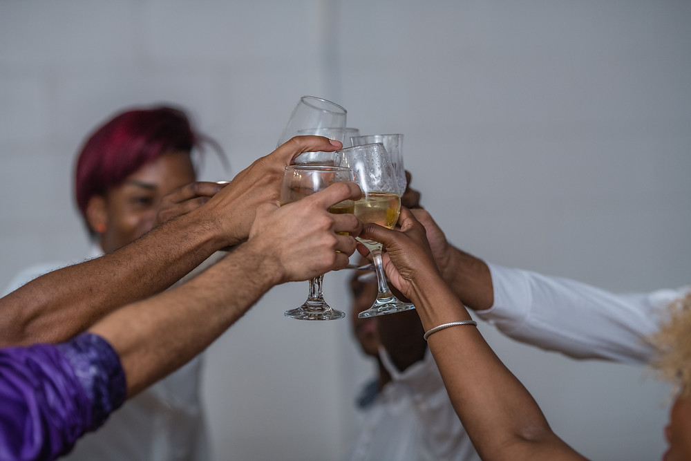 A shot of 6 hands of the two grooms and their guests (although you can't make out everyone) holding up wine glasses and toasting; big cheers for the couple and their wedding which was officiated by lgbtq+ officiant at Once Upon A Vow.!