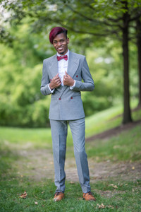 A young black man wearing a fitted charcoal grey suit with red wine accents, including a stylish red wine bow tie and red wine hair, smiling and standing tall with hands on his lapels standing in a grassy area in Brooklyn Bridge Park.