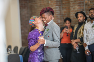 Two Caribbean grooms with clasped hands and wide smiles, the one wearing a purple dashiki-styled outfit has thrown his head backwards and closed his eyes laughing while the one in the grey-charcoal suit looking down laughing.