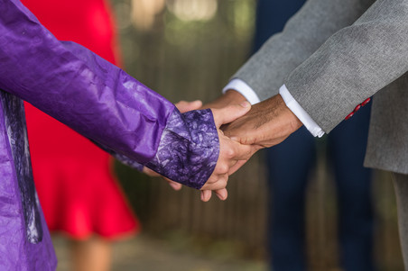 During Brooklyn ceremony officiated by queer officiant at Once Upon A Vow; close up shot of clasped hands of two black grooms holding hands, one wearing a formal purple dashiki-styled garment while the other wore a fitted charcoal grey suit with wine red buttons.