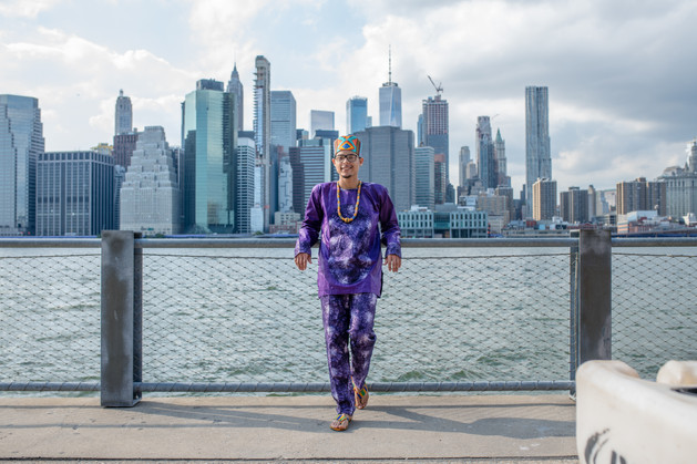 Groom wearing purple dashiki-styled outfit leaning against water barrier with NYC skyline behind him; pic taken post ceremony officiated by queer officiant at Once Upon A Vow.